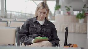 La femme vérifie l'email par le comprimé dans le hall de attente de la station, seul se reposant banque de vidéos