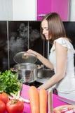 La femme vérifie la promptitude de nourriture Photographie stock libre de droits