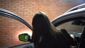 La femme va à sa voiture, ouvre la porte et s'assied dans elle clips vidéos