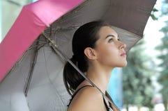 La femme va sous un parapluie images stock