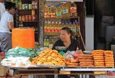 La femme vend des pâtisseries sur le marché, Hanoï Photo stock