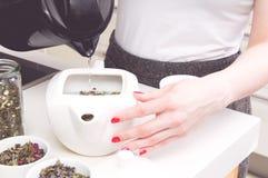 La femme a versé l'eau chaude dans la bouilloire Photo stock