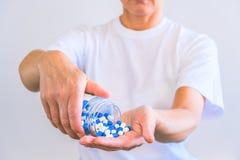 La femme a versé une poignée de capsules de sports dans la paume de sa main Réception avant la formation Augmentez la force et l' photo stock