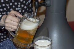La femme verse la bière froide fraîche d'un distributeur de refroidissement de table dans des verres de bière image libre de droits