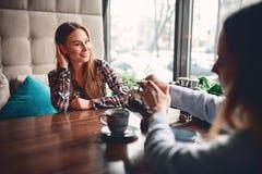La femme verse le café pour son amie en café Photographie stock libre de droits