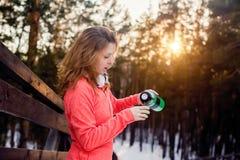 La femme verse le thé chaud dans une tasse d'un thermos Photo libre de droits