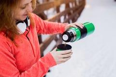 La femme verse le thé chaud dans une tasse de thermos Images stock