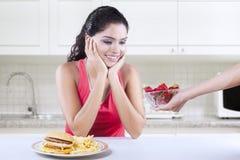 La femme veut la fraise plutôt que l'hamburger Photo stock