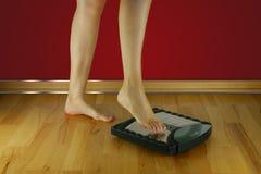 La femme veut peser et se tient sur les échelles photos stock