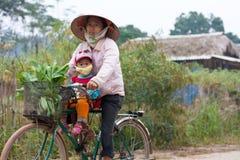 La femme vietnamienne conduit une bicyclette avec son enfant Images stock