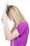La femmina è battimenti upset la sua testa dai scrittura-libri immagine stock