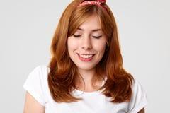 La femmina abbastanza giovane con compone e pelle pura sana, chiude gli occhi e sorride da piacere, ha tinto i capelli lunghi, ri fotografia stock libera da diritti