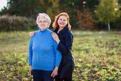 La femmina adulta abbraccia una madre anziana fotografie stock libere da diritti
