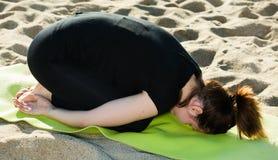 La femmina adulta in maglietta nera sta praticando l'insieme di allungamento ex Immagine Stock Libera da Diritti