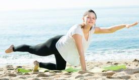La femmina adulta sorridente in maglietta bianca sta allungando Fotografie Stock Libere da Diritti
