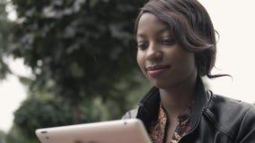 La femmina afroamericana giovane di risata che tiene un cuscinetto di tocco riduce in pani il PC all'aperto, studente nero dopo f Immagine Stock