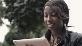 La femmina afroamericana giovane di risata che tiene un cuscinetto di tocco riduce in pani il PC all'aperto, studente nero dopo f Fotografia Stock
