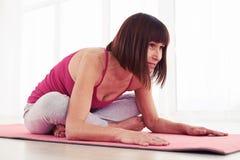 La femmina allunga con seduta attraversata gambe su una stuoia di yoga fotografie stock libere da diritti