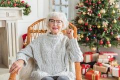 La femmina anziana allegra sta riposando a casa Immagine Stock