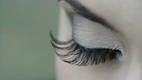 La femmina apre i suoi occhi verdi con trucco lungo delle sferze stock footage