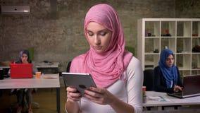 La femmina araba concentrata sta scrivendo sulla sua compressa mentre stava vicino ad altre ragazze arabe nell'ufficio moderno de stock footage