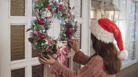 La femmina attraente nel Natale d'attaccatura del cappello si avvolge con le palle sulla porta in casa video d archivio
