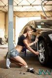 La femmina attraente ripara la ruota anteriore dell'automobile in garage immagini stock libere da diritti
