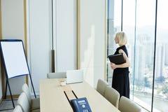 La femmina bionda sta aspettando il socio commerciale è il suo ufficio privato fotografie stock libere da diritti