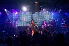 La femmina canta mentre la banda gioca in scena Fotografie Stock