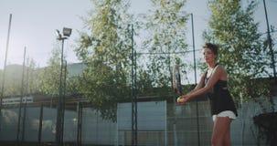 La femmina carismatica del tennis batte professionale la pallina da tennis sul campo da tennis video d archivio