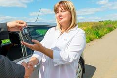 La femmina comprata una nuova automobile ed ottiene la chiave Fotografie Stock