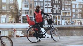 La femmina con la bicicletta sta sulla banchina vivace del fiume Tempo reale posteriore di vista Femmina europea del viaggiatore  archivi video