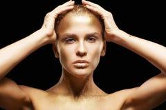 La femmina con le mani si avvicina al fronte Ragazza dorata su fondo nero fotografia stock
