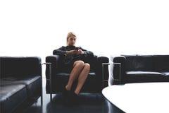 La femmina con stile fresco sta chiacchierando nelle reti sociali tramite telefono delle cellule mentre sedendosi nella sala di a Fotografia Stock Libera da Diritti