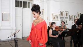 La femmina di Cantante in un vestito elegante entra nella stanza e va al microfono sull'orchestra sinfonica e sul conduttore del  stock footage
