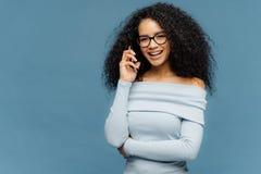 La femmina di Glad African American gode della conversazione telefonica, tiene uno consegna la vita, le tecnologie moderne di usi immagine stock libera da diritti