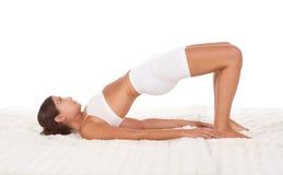 La femmina di posa di yoga nello sport copre fare l'esercitazione Immagini Stock