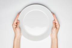 La femmina (donna) due mani tiene (supporto) un isolat bianco del piatto (piatto) immagini stock libere da diritti