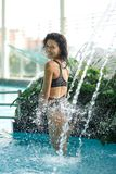 La femmina esile sexy in costume da bagno prende la doccia nella piscina fra i cespugli verdi sul tetto con il fondo dello scape  immagine stock