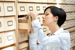 La femmina graziosa cerca qualcosa nel catalogo di scheda Fotografie Stock Libere da Diritti