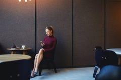 La femmina ha letto il messaggio di testo sul suo telefono cellulare mentre aspettando qualcuno nell'interno moderno del ristoran Fotografia Stock Libera da Diritti