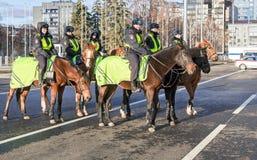 La femmina ha montato la polizia sul cavallo indietro alla via della città Fotografia Stock