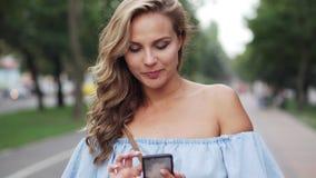 La femmina legge i messaggi sullo smartphone e sorride