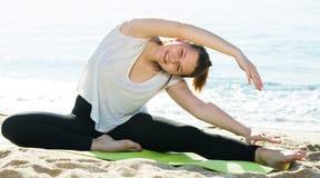 La femmina in maglietta bianca sta praticando l'insieme di allungamento dell'esercizio Immagini Stock