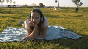 La femmina mette sull'erba nel parco ed ascoltare la musica in cuffie fotografie stock