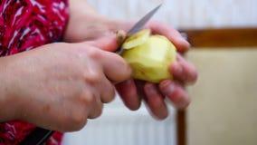 La femmina passa il primo piano Patate della sbucciatura del coltello video d archivio