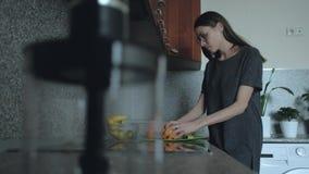 La femmina prepara la prima colazione di mattina nella cucina Una donna taglia la frutta, arancio sulla tavola archivi video