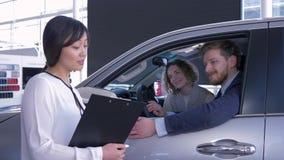 La femmina professionale di Asian del responsabile informa la giovane famiglia dei compratori che si siede nel salone dell'automo