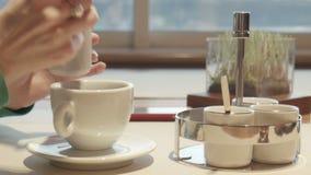 La femmina riempie lo zucchero in caffè e nelle scalpore stock footage