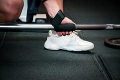 La femmina si prepara per l'esercizio del deadlift con la barra del peso Immagine Stock